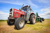 Tracteur collecte un rouleau de botte de foin dans le domaine — Photo