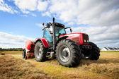 трактор, собирая стог сена в поле, панорамирование техника — Стоковое фото