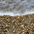 Pebbles on beach with sea wave — Stock Photo