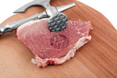 Meat cleaver in fresh pork chops — Stock Photo