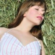 Woman lying in dry grass — Stock Photo