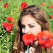 Girl through high poppies — Stok fotoğraf