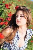 Tender girl in field of poppy — Stock Photo