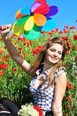 Girl with windmill in poppy field — Stock Photo