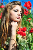 Pensive girl in poppy field — Stock Photo