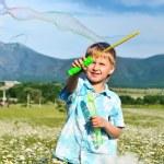 Boy blowing soap bubbles — Stock Photo #7260196