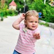 Baby girl catching soap bubbles — Stock Photo #7260233