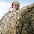 Young woman and huge haystack — Stock Photo