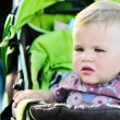 Serious girl in stroller — Stock Photo