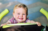 Baby girl having fun in the stroller — Stock Photo