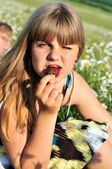 Girl liking strawberry — Stock Photo