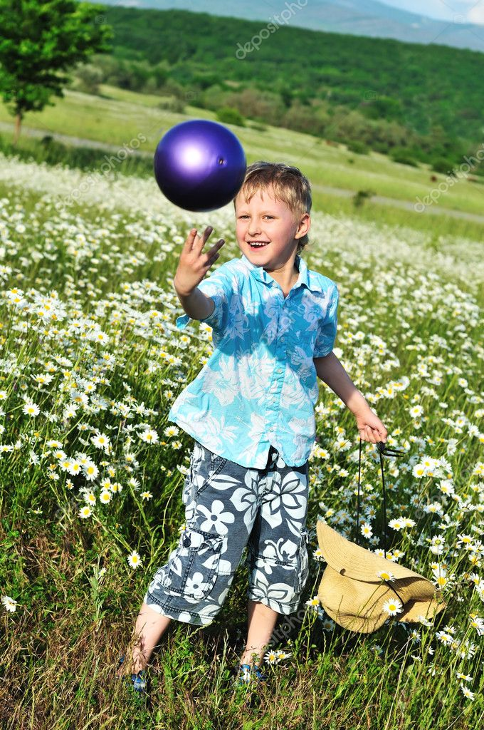 Funny boy playing ball at the daisy field  — Stock Photo #7260311