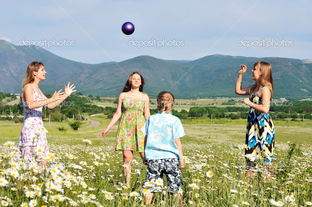 Boy and teen girls playing a ball in field   Stock Photo #7260925