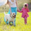 Happy family walking with dog — Stock Photo