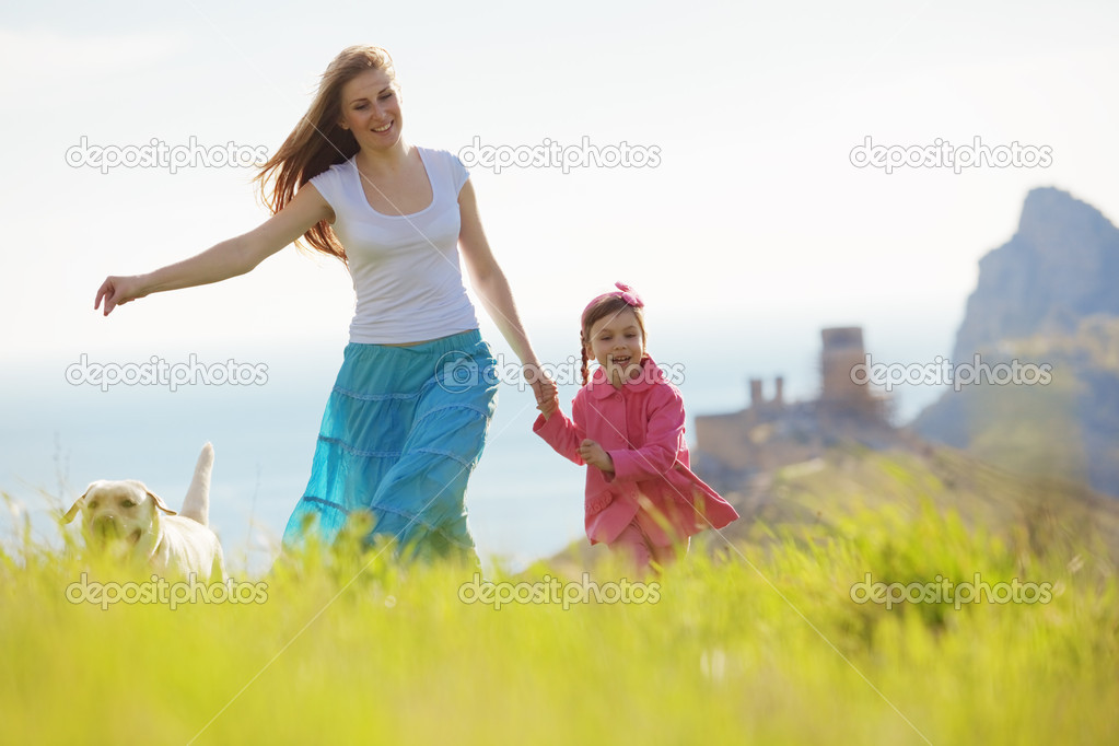 Happy family walking with dog in green field — Stock Photo #6802804