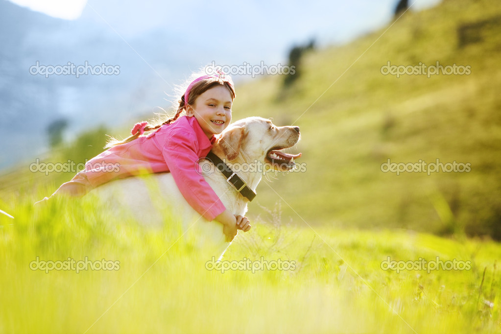 Happy child playing with dog in green field  Lizenzfreies Foto #6802825