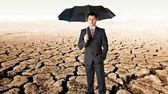 Bussinessman with umbrella in a desert — Stock Photo