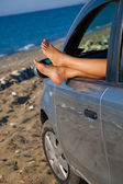Woman's legs dangling out a car window — Stock Photo