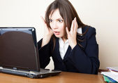 Frightened woman is looking at the laptop screen — 图库照片