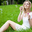 Woman is blowing soap bubbles — Stock Photo