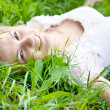 Beautiful girl is lying on green grass — Stock Photo