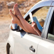 Woman's legs are dangling out a car window - Stock Photo