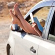 Stock Photo: Woman's legs are dangling out a car window