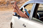 Woman's legs are dangling out a car window — Stockfoto