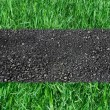 Asphalted road on green grass - Stock Photo