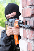 Soldier in black mask targeting with a gun — Stockfoto