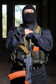 Soldier in black mask holding AK-47 gun — Stock Photo