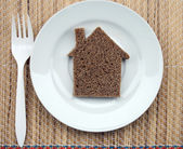 House carved out of bread lying on a plate. — Stock Photo