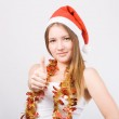 Girl in Santa hat showing thumbs up. — Stock Photo