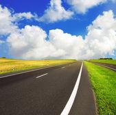 Camino de asfalto sobre cielo azul — Foto de Stock