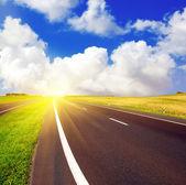 Asphalt road over blue sky — Stock Photo