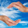 Stock Photo: Female hands over blue sky with clouds