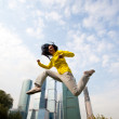 Brunette in a yellow blazer jumping — Stock Photo