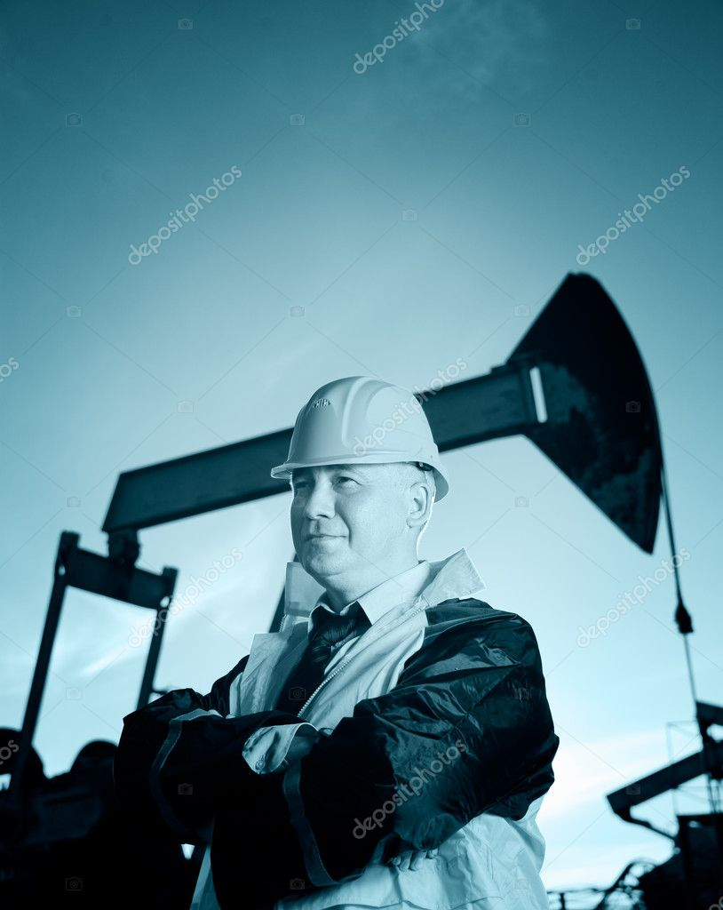 Oil worker in uniform and helmet on of background the pump jack and sky. Toned.  Stock Photo #7651313