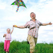 Father with daughter playing with kite — Stock Photo