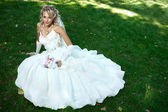 Bride in white dress on green grass — Stock Photo