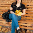 Beautiful girl with autumn leaves sitting on a bench in autumn p — Stock Photo #7498101