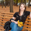 Beautiful girl sitting on a bench in autumn park — Stock Photo #7498106