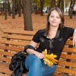 Beautiful girl sitting on a bench in autumn park — Stock Photo