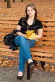 Beautiful girl with autumn leaves sitting on a bench in autumn p — Stock Photo