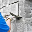 Hand holding knife applying paint and plaster on wall. — Stock Photo #7678644