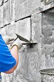 Una mano sosteniendo un cuchillo aplicar pintura y yeso en una pared. — Foto de Stock