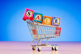 Mini shopping cart against gradient background — Stock Photo
