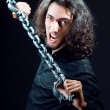 Man chained in the dark room — Stock Photo
