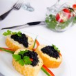 Black caviar served on bread - Stock Photo