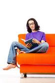 Student som läser boken på soffa — Stockfoto